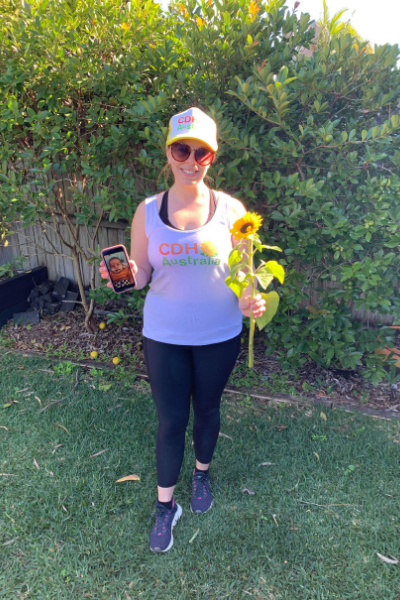 Woman standing in garden holding a phone and a sunflower